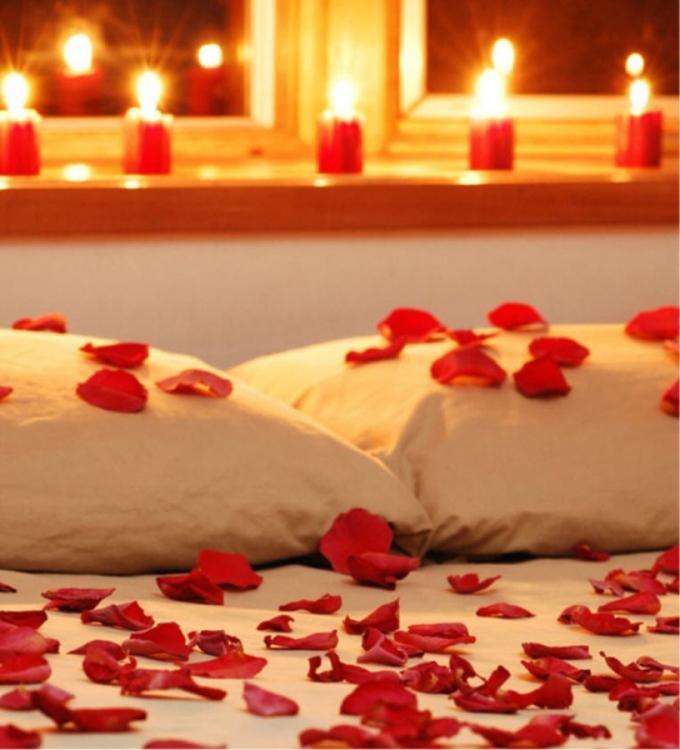 Свечи и лепестки роз в спальне