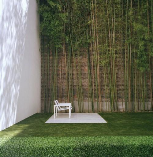 Зеленый уголок возле кирпичной стены
