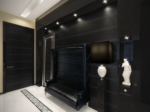 Черный диван возле темной стенки