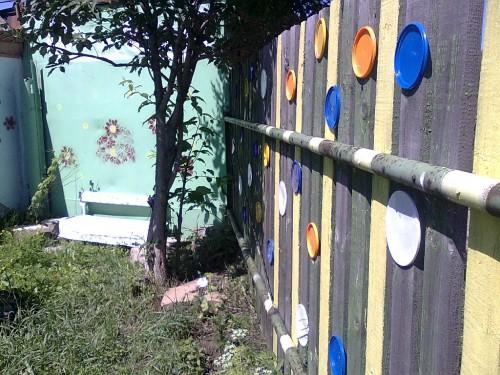 Декорирование забора разноцветными пластиковыми тарелками