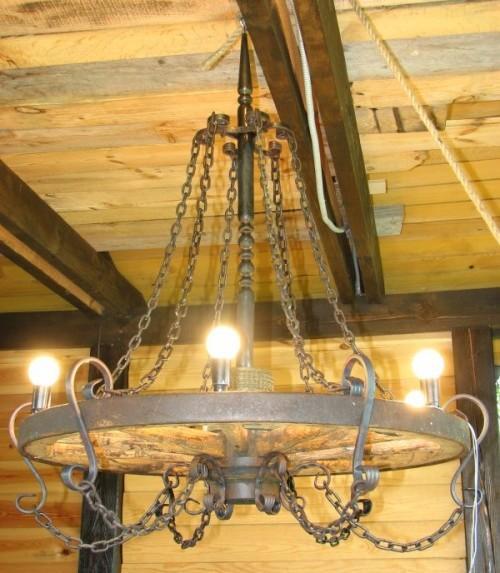 Люстра из колеса телеги в деревянном доме