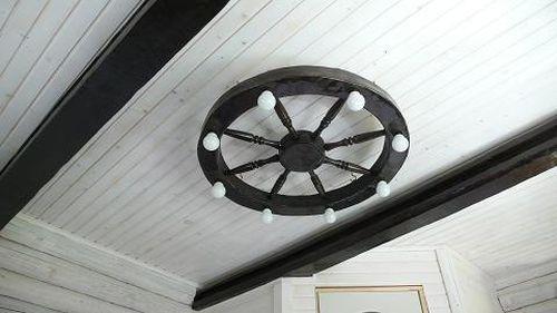 Люстра-колесо в интерьере комнаты