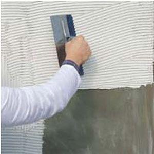 Наносимо клей на стіну для приклеювання мозаїки